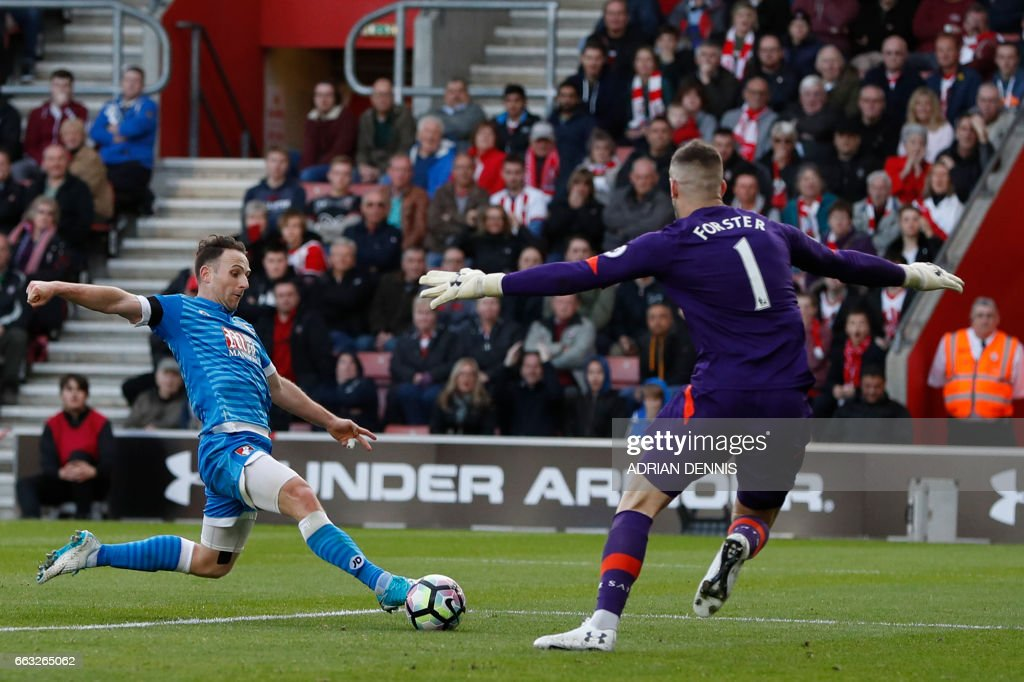 Bournemouth's English midfielder Marc Pugh (L) shoots as Southampton's English goalkeeper Fraser Forster prepares to save during the English Premier League football match between Southampton and Bournemouth at St Mary's Stadium in Southampton, southern England on April 1, 2017. The game finished 0-0. / AFP PHOTO / Adrian DENNIS / RESTRICTED TO EDITORIAL USE. No use with unauthorized audio, video, data, fixture lists, club/league logos or 'live' services. Online in-match use limited to 75 images, no video emulation. No use in betting, games or single club/league/player publications. /