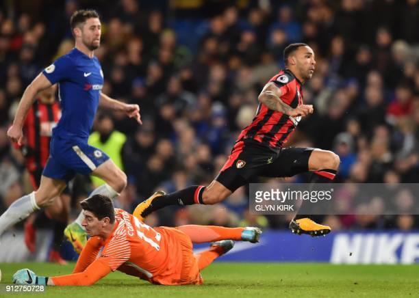 Bournemouth's English striker Callum Wilson leaps past Chelsea's Belgian goalkeeper Thibaut Courtois after scoring the team's first goal during the...