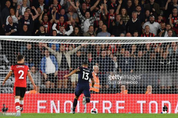 Bournemouth's English striker Callum Wilson puts the ball into the empty net to score their late third goal during the English Premier League...