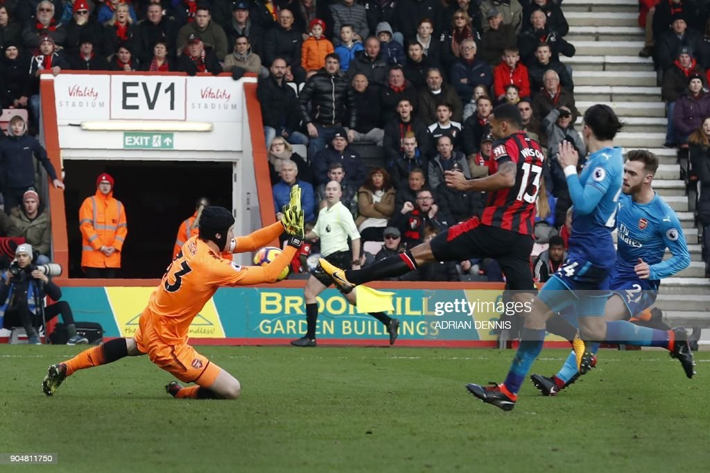 Bournemouth's English striker Callum Wilson (C) scores his team's first goal past Arsenal's Czech goalkeeper Petr Cech during the English Premier League football match between Bournemouth and Arsenal at the Vitality Stadium in Bournemouth, southern England on January 14, 2018. / AFP PHOTO / Adrian DENNIS / RESTRICTED TO EDITORIAL USE. No use with unauthorized audio, video, data, fixture lists, club/league logos or 'live' services. Online in-match use limited to 75 images, no video emulation. No use in betting, games or single club/league/player publications. /