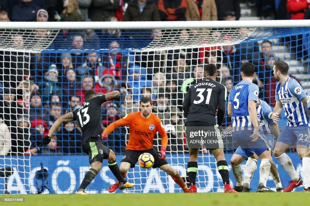 Bournemouth's English striker Callum Wilson (L) scores their second goal after a goal-mouth scramble during the English Premier League football match between Brighton and Hove Albion and Bournemouth at the American Express Community Stadium in Brighton, southern England on January 1, 2018. / AFP PHOTO / Adrian DENNIS / RESTRICTED TO EDITORIAL USE. No use with unauthorized audio, video, data, fixture lists, club/league logos or 'live' services. Online in-match use limited to 75 images, no video emulation. No use in betting, games or single club/league/player publications. /