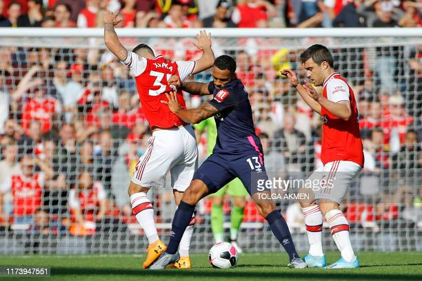 Bournemouth's English striker Callum Wilson vies with Arsenal's Swiss midfielder Granit Xhaka and Arsenal's Greek defender Sokratis Papastathopoulos...