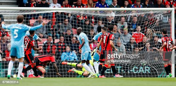 Bournemouth's French midfielder Lys Mousset watches the ball after scoring an own goal during the English Premier League football match between...