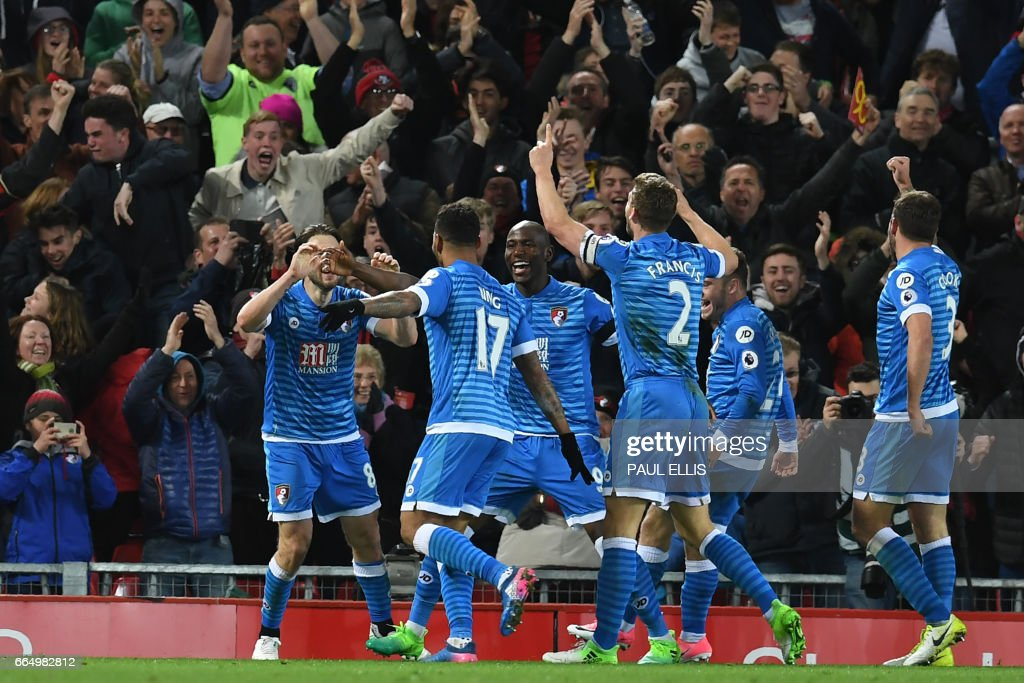 Bournemouth's Norwegian striker Joshua King (2nd L) celebrates with teammates after scoring their second goal during the English Premier League football match between Liverpool and Bournemouth at Anfield in Liverpool, north west England on April 5, 2017. The game finished 2-2. / AFP PHOTO / Paul ELLIS / RESTRICTED TO EDITORIAL USE. No use with unauthorized audio, video, data, fixture lists, club/league logos or 'live' services. Online in-match use limited to 75 images, no video emulation. No use in betting, games or single club/league/player publications. /