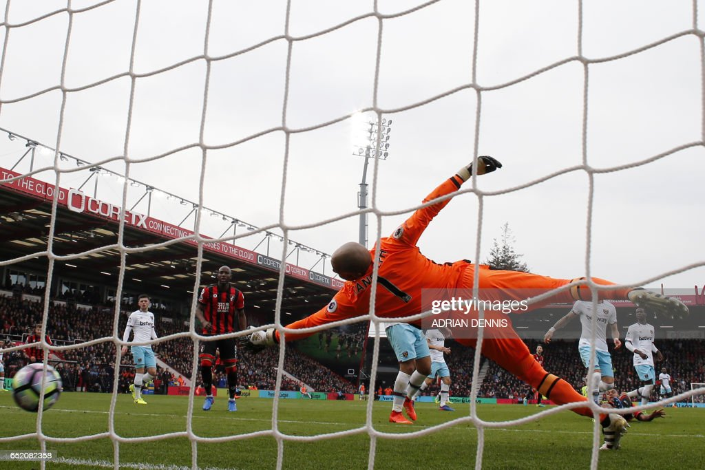 Bournemouth's Norwegian striker Joshua King (R) scores their first goal past the dive of West Ham United's Irish goalkeeper Darren Randolph during the English Premier League football match between Bournemouth and West Ham United at the Vitality Stadium in Bournemouth, southern England on March 11, 2017. / AFP PHOTO / Adrian DENNIS / RESTRICTED TO EDITORIAL USE. No use with unauthorized audio, video, data, fixture lists, club/league logos or 'live' services. Online in-match use limited to 75 images, no video emulation. No use in betting, games or single club/league/player publications. /