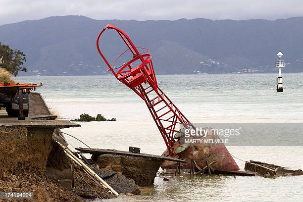 A bout that used to be on the edge of the road sits in the harbour where the land fell into the sea at the Port Wellington Container terminal caused...