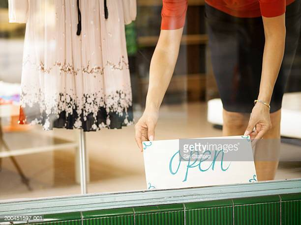 Boutique salesperson placing open sign on window