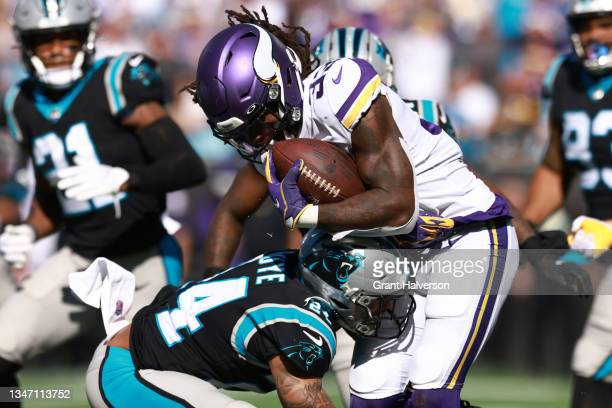 Bouye of the Carolina Panthers tackles Dalvin Cook of the Minnesota Vikings during the third quarter at Bank of America Stadium on October 17, 2021...