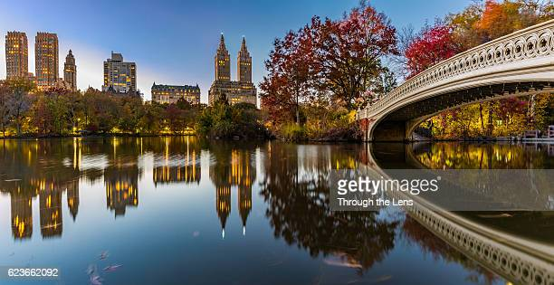 bow bridge panorama at central park during dusk - footbridge stock photos and pictures