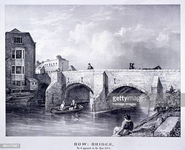 Bow Bridge, Poplar, London, 1834. The bridge over the River Lea at Bow; two men pass under an arch in a rowing-boat, a boy fishes from the bank,...