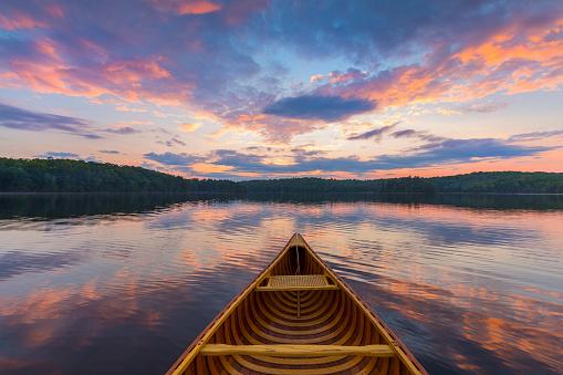 Bow of a cedar canoe on a lake at sunset - Ontario, Canada 839989380
