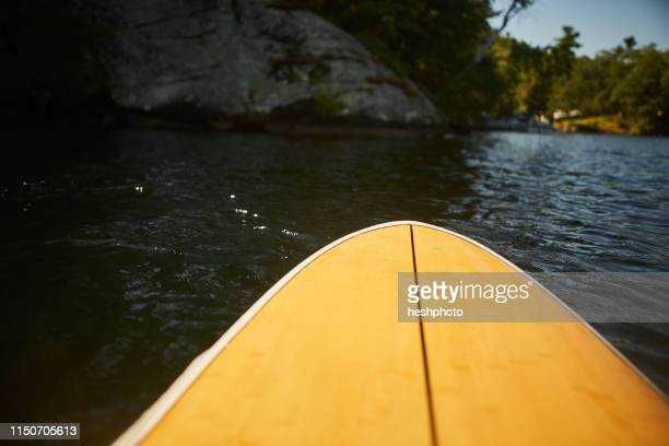bow of paddle board in lake - heshphoto stock pictures, royalty-free photos & images
