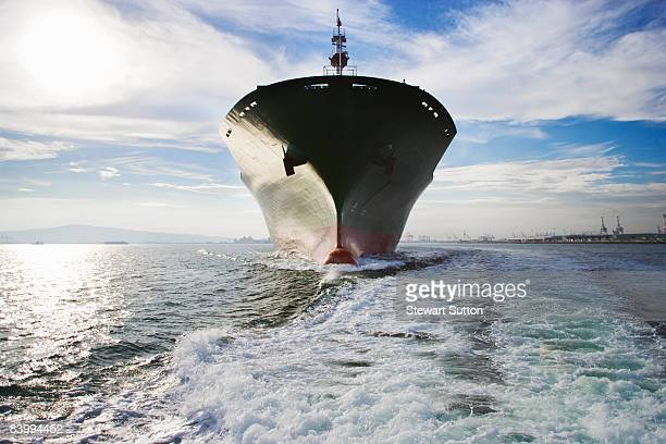 Bow view of cargo ship sailing out of port.