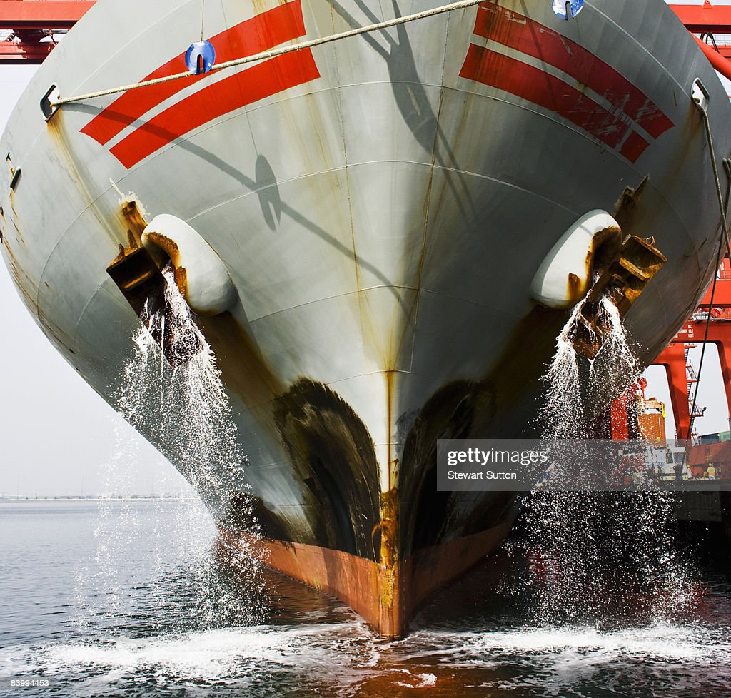 Bow view of docked cargo ship deck being flushed. : Stock Photo