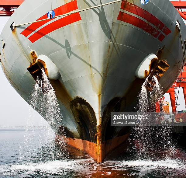 Bow view of docked cargo ship deck being flushed.