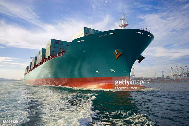 Bow view of loaded cargo ship sailing out of port.