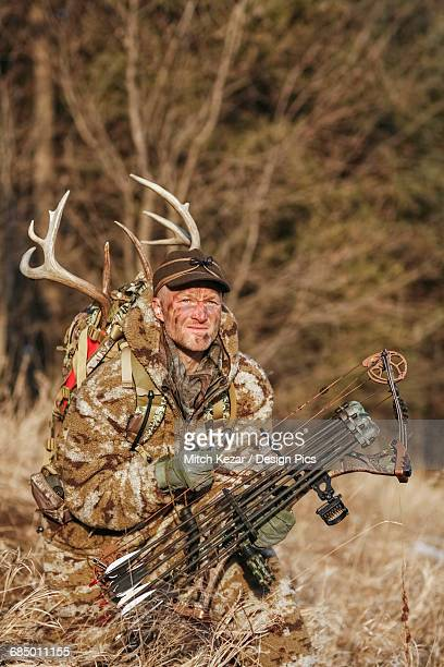 Bowhunter In Camo Clothing hunting Whitetail Deer