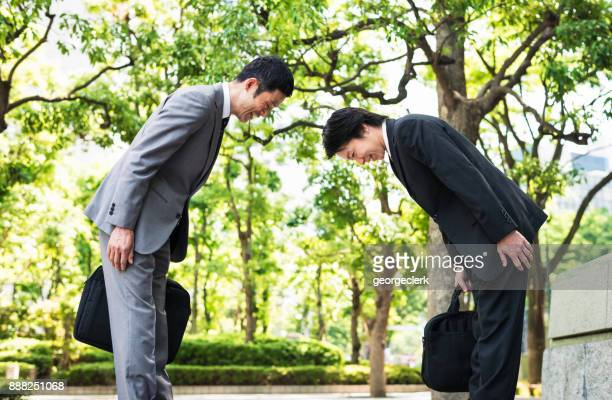 bowing - two japanese businessmen greeting each other in tokyo - humility stock pictures, royalty-free photos & images