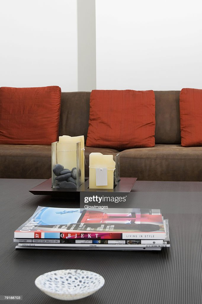 Bowl and magazines on a table in front of a couch : Foto de stock