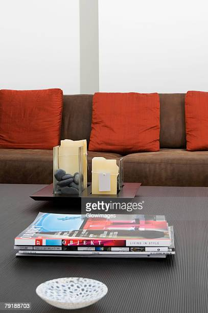 Bowl and magazines on a table in front of a couch