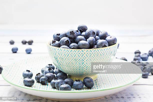 Bowl and plate of blueberries on wood
