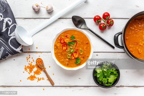 bowl and pot of garnished red lentil soup and ingredients on white wood - soup stock pictures, royalty-free photos & images