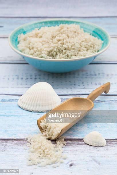 Bowl and shovel of Guerande sea salt and seashells on wood