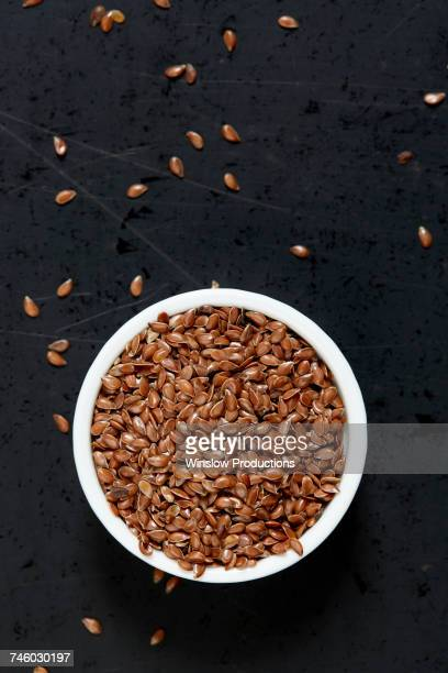 Bowl full of flax seeds on black background