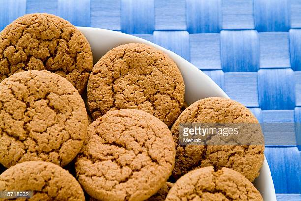 Bowl full of ginger snaps on blue tablecloth