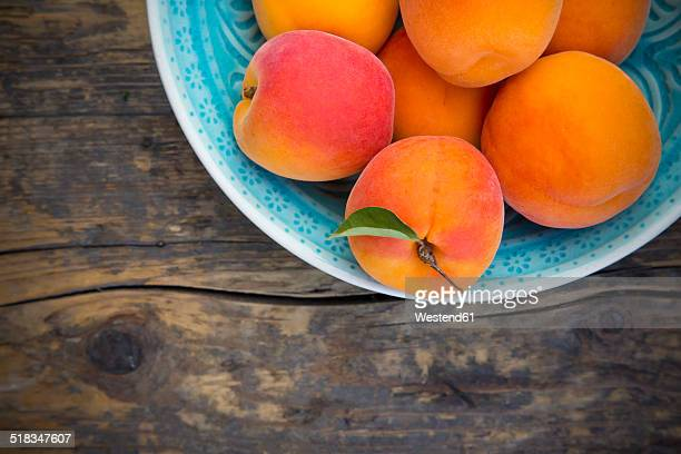 Bowl of apricots on wood, partial view