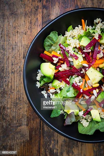 Bowl of autumnal salad with lettuce, carrots, avocado, beetroot, pumpkin and sunflower seeds, pomegranate and quinoa
