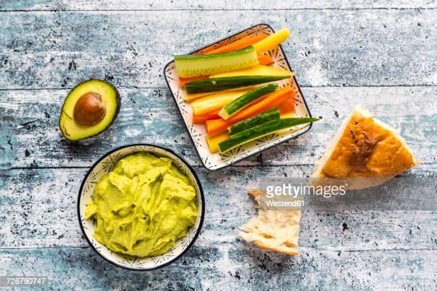 Bowl of avocado hummus, crudites, avocado and flat bread