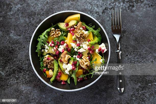 bowl of avocado salad with rocket, pomegranate seed, kaki, feta and walnuts - nut food stock photos and pictures
