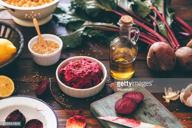 Bowl of Beetroot Hummus and ingredients on wood