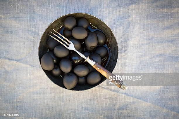 Bowl of black olives and fork on cloth