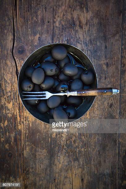 Bowl of black olives and fork on dark wood