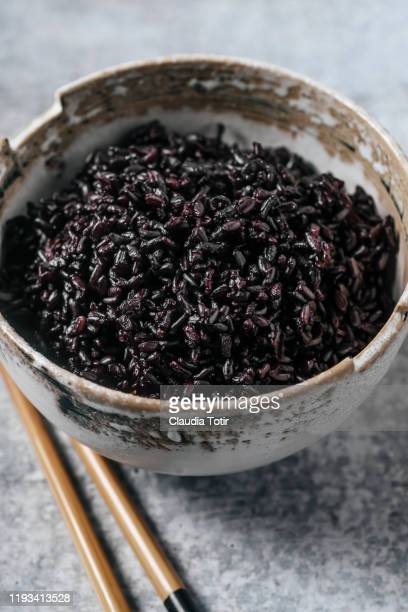 bowl of black rice with chopsticks on gray background - black rice stock pictures, royalty-free photos & images