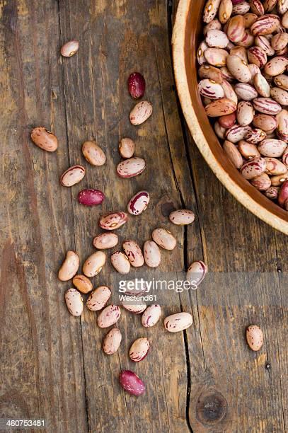 Bowl of borlotti beans on wooden table, close up