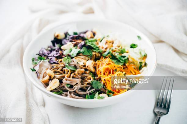 Bowl of buckwheat noodle salad with raw vegetables, roasted cashews,  coriander and spicy dressing