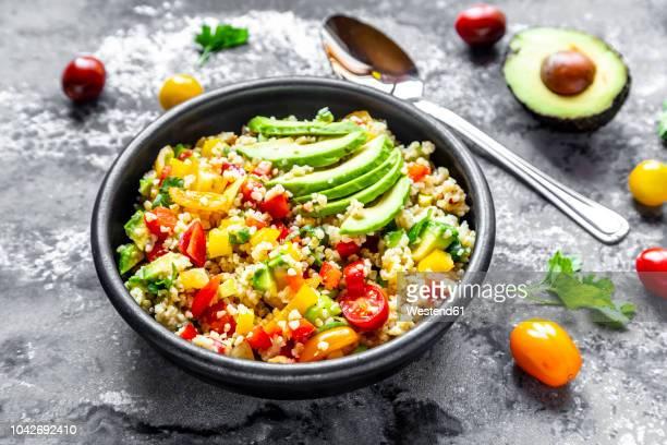 bowl of bulgur salad with bell pepper, tomatoes, avocado, spring onion and parsley - bulgur bildbanksfoton och bilder