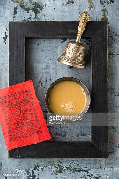 Bowl of butter tea, red prayer flag, black picture frame and bell on grey ground
