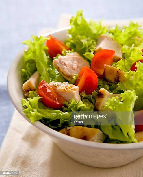Bowl of Caesar salad showing chicken, tomato and lettuce