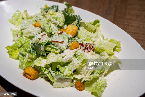 a bowl of caesar salad with croutons and cheese on table - side salad stock pictures, royalty-free photos & images