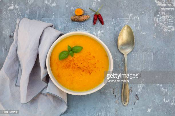 bowl of carrot turmeric soup with ginger, chili and basil