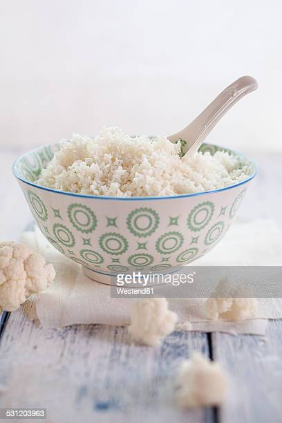 bowl of cauliflower rice and cauliflower florets on cloth and wood - boiled stock pictures, royalty-free photos & images