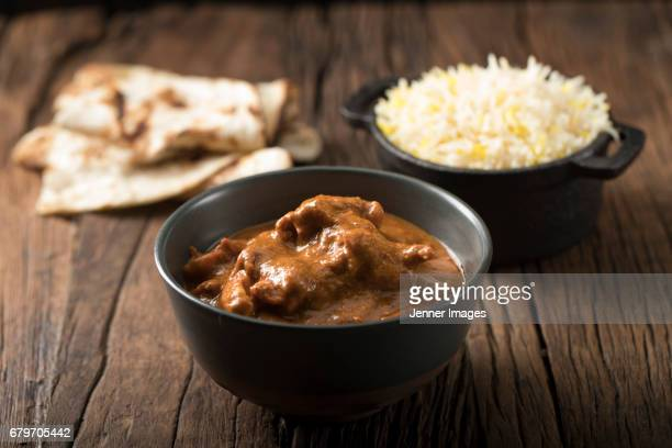 bowl of chicken curry with naan and rice. - chicken masala stock photos and pictures