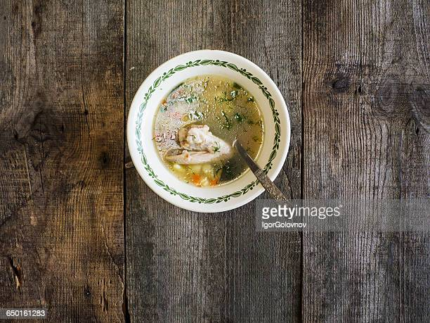 Bowl of chicken soup on wooden table