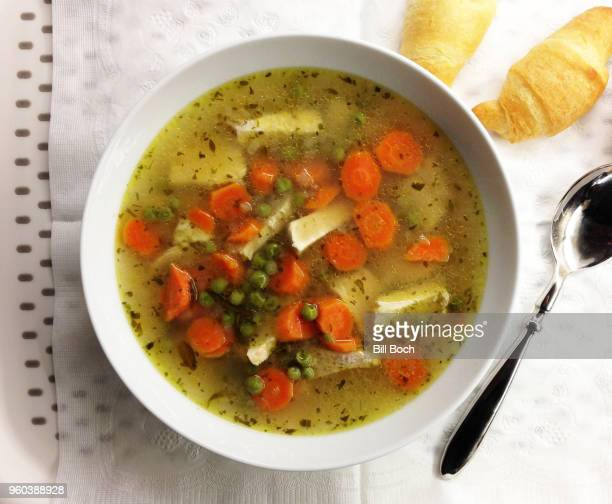 bowl of chicken soup with tarragon on a tray with a paper napkin, spoon, and crescent rolls - chicken soup stock photos and pictures