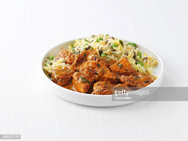 Bowl of chicken tikka masala and peas with steamed rice