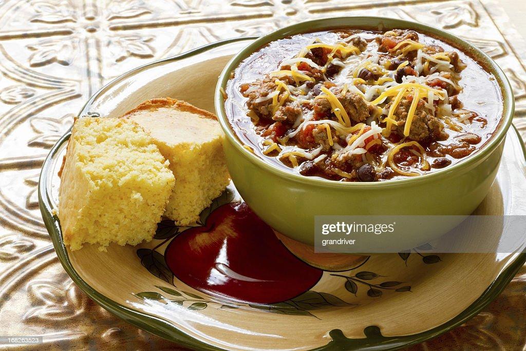 Tigela de Chili com queijo ralado e pão de milho : Foto de stock